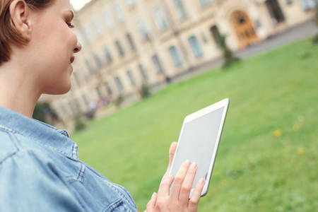 Young student at university campus stnading browsing digital tablet happy back view close-up Stock Photo