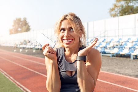 Sporty Lifestyle. Young woman on stadium hands aside with smartphone smiling excited close-up Stock fotó