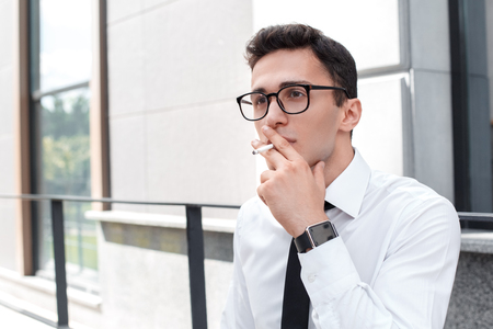 Bad habit. Businessman in eyeglasses leaning on wall on the city street smoking close-up