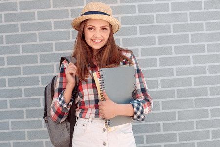 Young girl in hat with backpack and notebooks smiling toothy isolated on grey wall Imagens