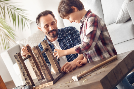 Father and little son at home standing screwing nail with screwdriver happy teamwork Stockfoto