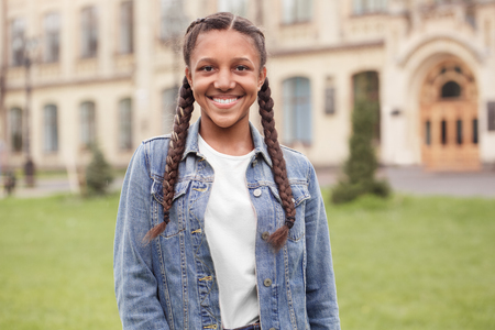 Young schoolgirl in jeans standing at school yard looking camera cheerful close-up