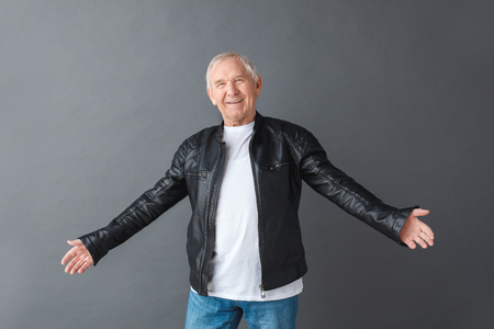 Senior man in leather jacket standing isolated on gray opening hands looking camera friendly