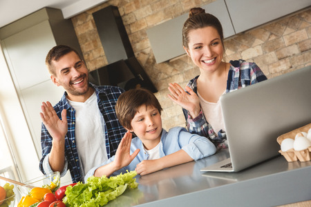 Family at home standing in kitchen together using video chat on laptop waving to camera cheerful