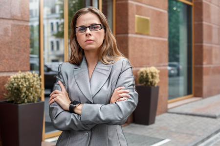 Business woman in eyeglasses standing on the city street crossed arms impudent