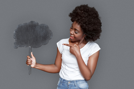Young woman standing isolated on gray pointing at cloud smiling playful 스톡 콘텐츠