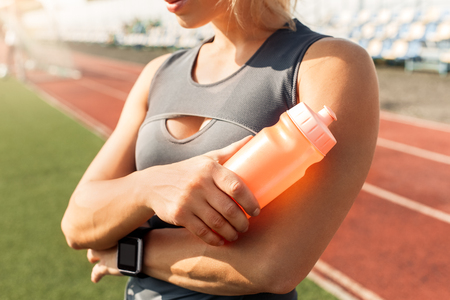 Young woman athlete on stadium sporty lifestyle standing crossed arms holding bottle of water wearing digital watch close-up