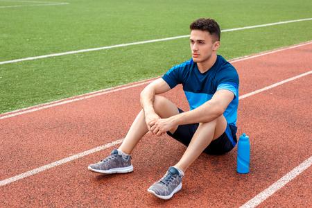 Po przerwie. Młody mężczyzna na stadionie na zewnątrz siedzi z butelką wody Zdjęcie Seryjne