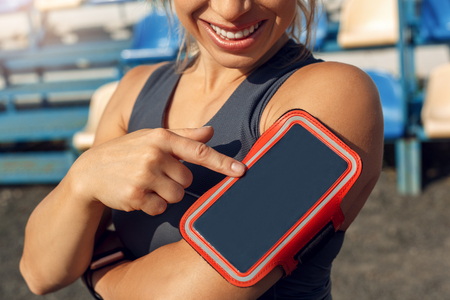 Young woman athlete wearing armband standing on stadium sporty lifestyle touching smartphone screen protector smiling happy close-up Stockfoto