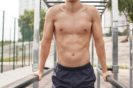 Young sportsman shirtless maintaining healthy lifestyle exercising outdoors doing push ups on bars torso close-up Stock fotó