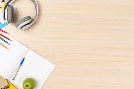 Draufsicht des hölzernen Schreibtischarbeitsplatzes niemand Kopfhörer-Notizbuch und Schreibwaren am Eckkopierraum Standard-Bild