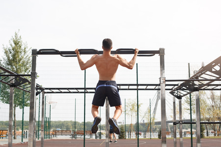 Young sportsman shirtless maintaining healthy lifestyle exercising outdoors doing pull ups on bar back view