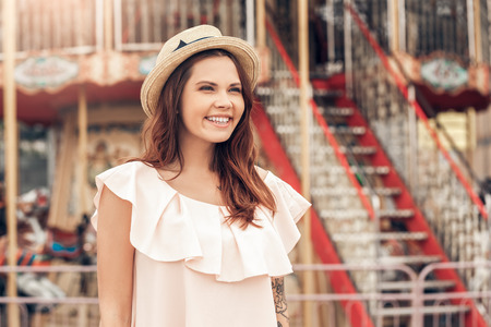 Ourdoors Leisure. Girl in hat standing at amusement park looking aside laughing playful