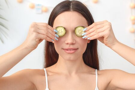 Young woman at home beauty care sitting covering eyes with cucumber smiling close-up