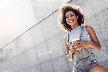 Young woman wearing overall shorts in the city street sitting holding latte laughing joyful