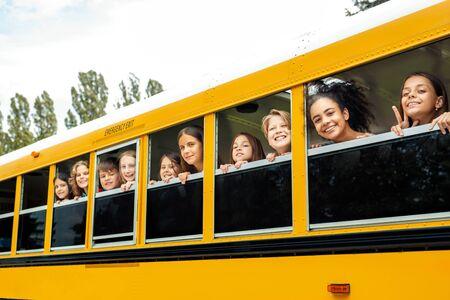 Koledzy z klasy jadący do szkoły autobusem wychylający się przez okno uśmiechający się radośnie Zdjęcie Seryjne
