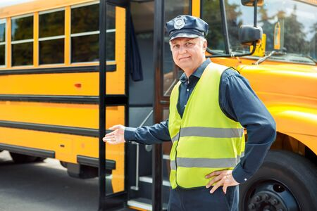 Senior driver standing near school bus showing door smiling friendly