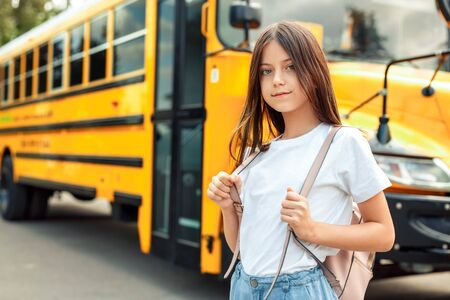 Kid with bag standing near bus going to school posing to camera pensive close-up