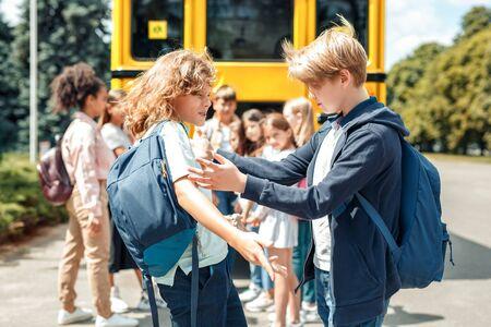Compagni di classe che vanno a scuola con il ragazzo dell'autobus che spingono il suo amico in un primo piano aggressivo