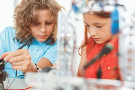 Robotics. Children sitting having class working together on robots concentrated close-up