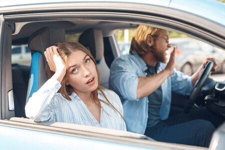 Angry young adult man and tired woman sitting in car
