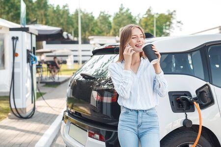 Junge erwachsene Frau, die Kaffee trinkt, Elektroauto auflädt, auf Smartphone spricht Standard-Bild