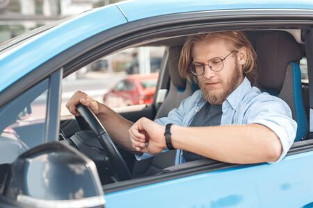 Young adult man sitting in car, looking on watch Stock Photo