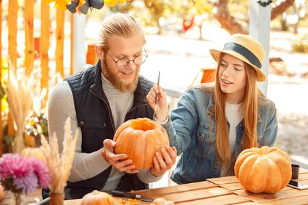 Halloween Preparaton Concept. Young couple sitting at table outdoors making jack-o-lantern painting face on pumpkin smiling inspired Imagens
