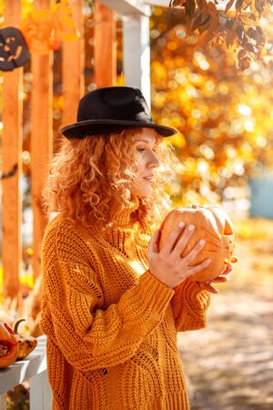Halloween Preparaton Concept. Young woman in hat standing outdoors with jack-o-lantern pensive