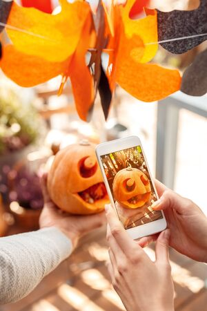 Young couple man and woman taking photo of jack-o'-lantern on smartphone preparing for halloween close-up