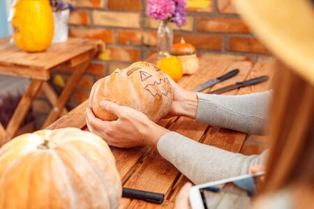 Young couple man holding pumpkin with face drawn while woman holding smartphone to take photo sitting at table at porch at vacation home outdoors making jack-o'-lantern preparing for halloween close-up