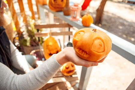 Young man standing decorating vacation house with jack-o'-lantern preparing for halloween holding pumpkin face close-up Imagens