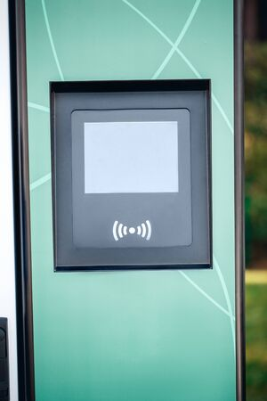 Blank screen display with copy space and wireless payment system. Public charging station for electric car. Eco-friendly and alternative energy concept Фото со стока