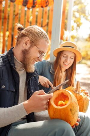 Halloween Preparaton Concept. Young couple outdoors making jack-o-lantern carving pumpkins smiling joyful side view close-up