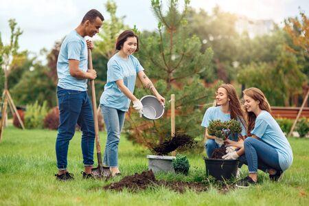 Faire du bénévolat. Les jeunes volontaires à l'extérieur plantant des arbres versant de l'engrais dans la fosse happy motion