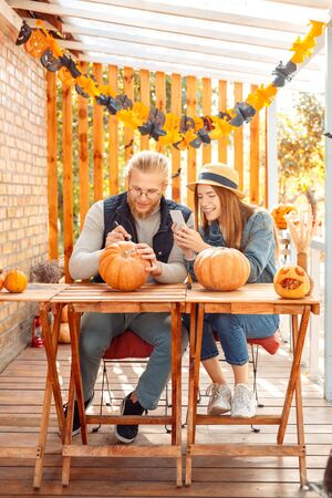 Halloween Preparaton Concept. Young couple sitting at table at porch making jack-o-lantern man drawing face on pumpkin while woman taking photo on smartphone cheerful Imagens