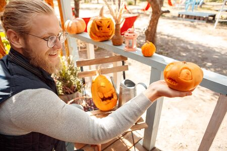 Halloween Preparaton Concept. Young man in glasses decorating house with jack-o-lantern holding pumpkin smiling cheerful Imagens