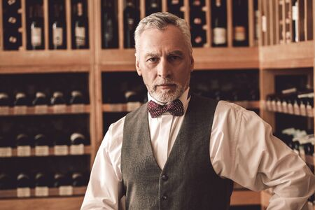 Sommelier Concept. Senior man standing looking camera serious close-up Foto de archivo