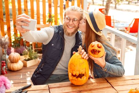 Halloween Preparaton Concept. Young couple sitting at table outdoors making jack-o-lantern man taking selfie on smartphone posing with carved pumpkins to camera laughing cheerful while woman kissing him