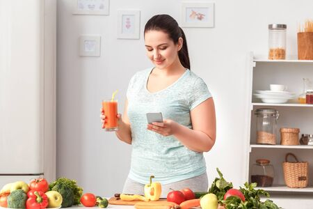 Cooking Meal. Chubby girl standing in kitchen drinking smoothie browsing smartphone joyful