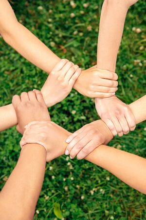 Volunteering. Young people volunteers outdoors together holding hands unity top view close-up Stock fotó