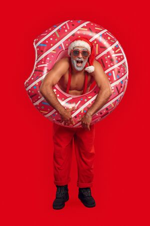 Handsome Santa Claus in sun glasses standing with inflatable ring for pool Stock Photo
