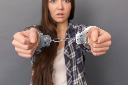 Freestyle. Young woman in cuffs standing studio isolated on grey close-up blurred background scared Banco de Imagens