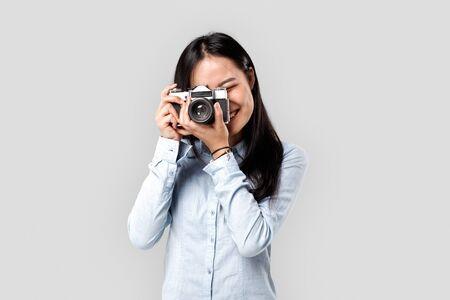 Chica asiática adulta joven que hace la foto en la cámara vieja