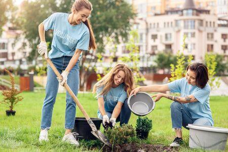 Ehrenamtliches Engagement. Junge Leute Freiwillige im Freien, die Bäume pflanzen, Boden graben und Wasser fröhlich gießen