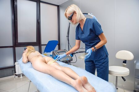 Cosmetology Service. Young woman at beauty clinic lying on medical bed while doctor in safety goggles applying cooling gel on back of hips