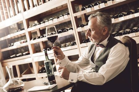 Sommelier Concept. Senior man sitting at table checking sediment in glass of red wine concerned