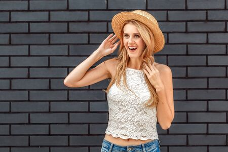 Freestyle. Young woman in hat standing isolated on wall looking aside surprised