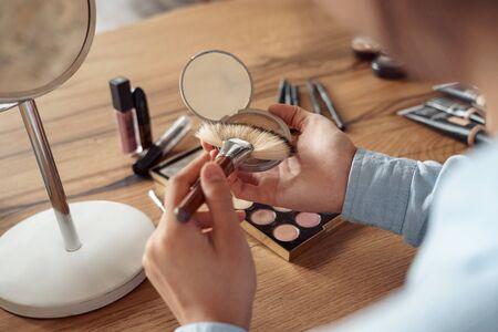 Freestyle. Asian girl makeup artist sitting applying bronzer close-up