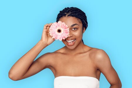 Beauty Concept. Young african woman isolated on blue covering eye with flower smiling playful Stock Photo